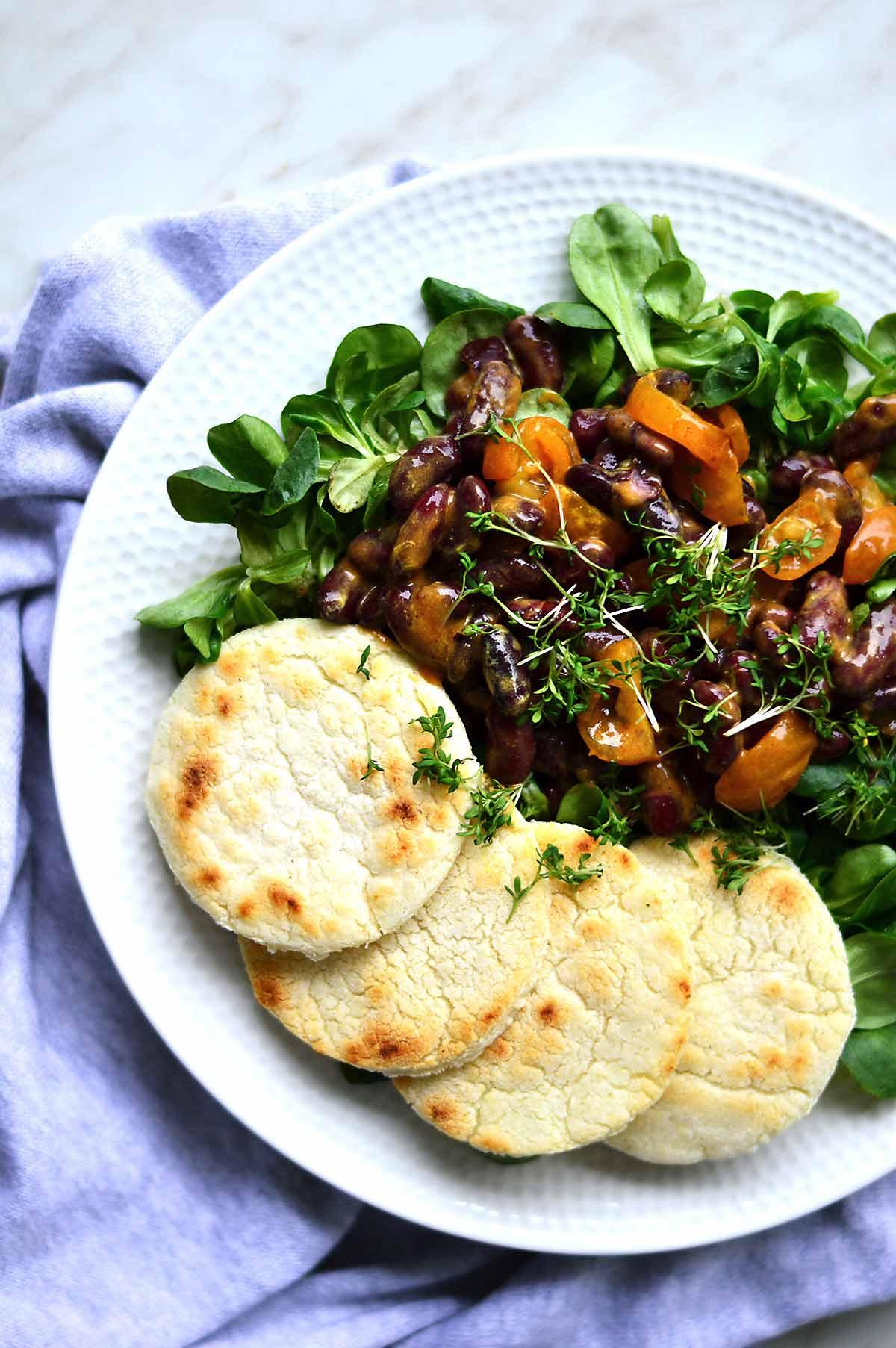 Plato con ensalada de alubias y arepas