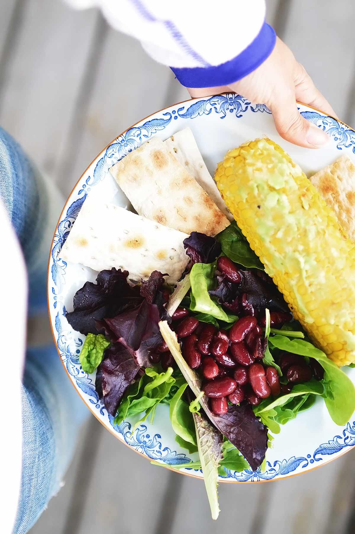 plato con mazorca de maíz, legumbres y ensalada