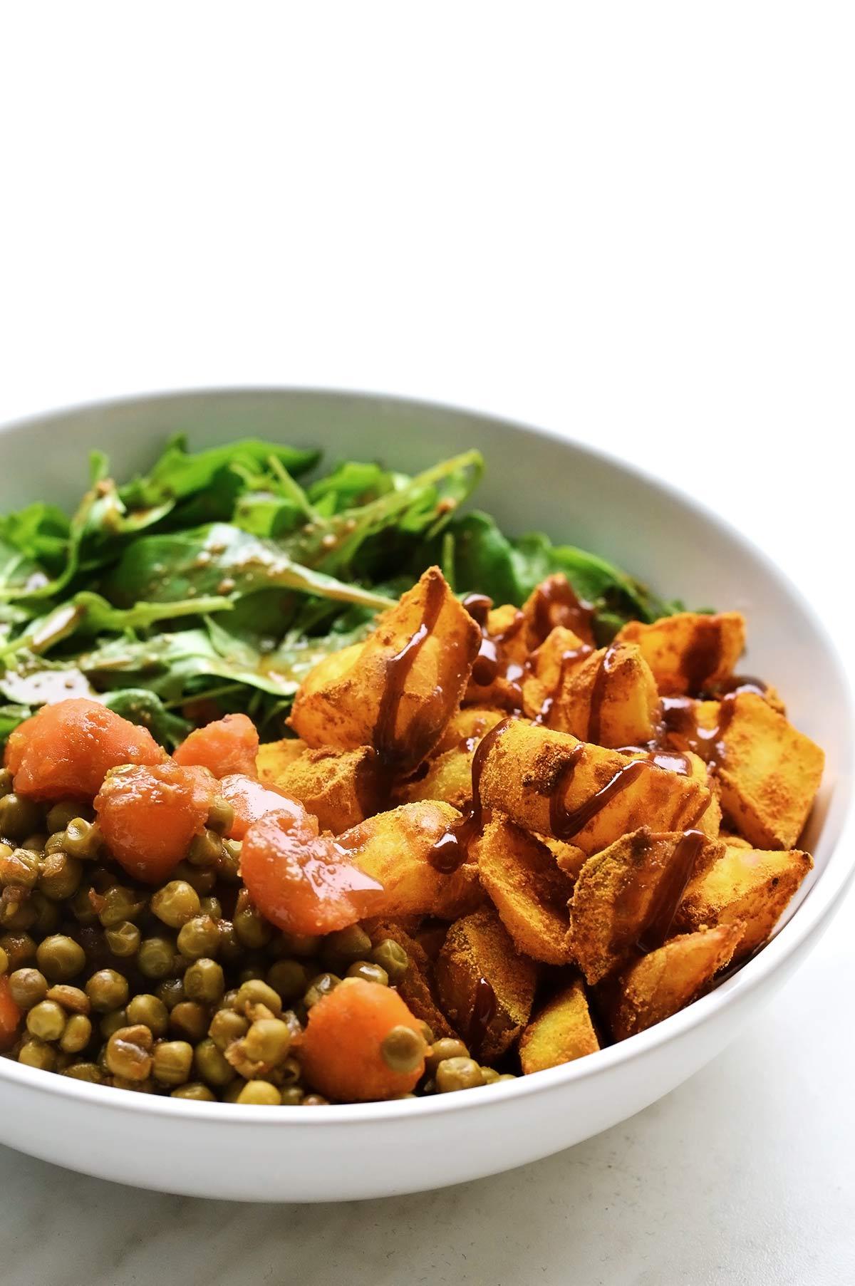 bol con patatas, guisantes y verdura de hoja verde