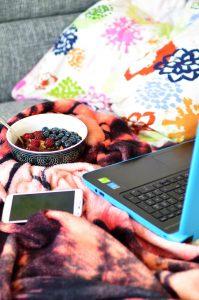 porridge, portátil y móvil en el sofá