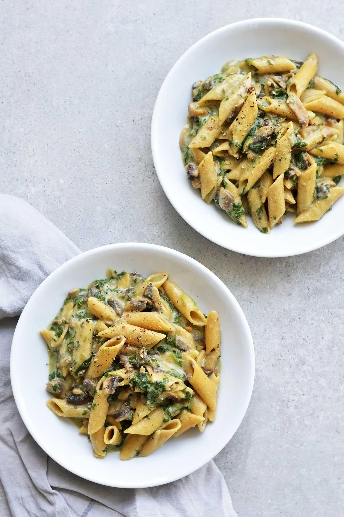 dos platos de pasta a la crema con espinacas y champiñones