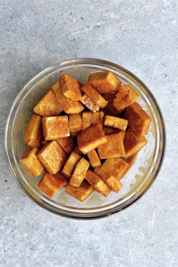 tofu frito sin aceite macerando en un bol de cristal