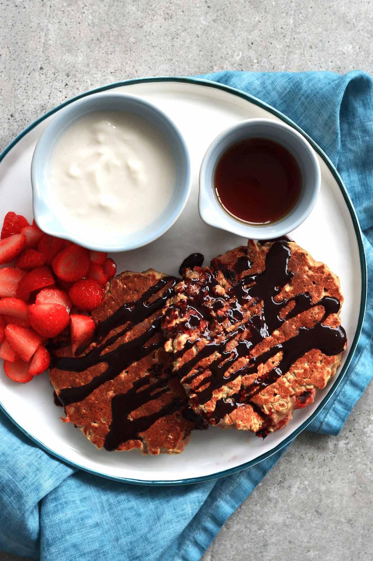 Pancakes de fresa y avena servidos con jarabe de arce, yogurt y fresas picadas