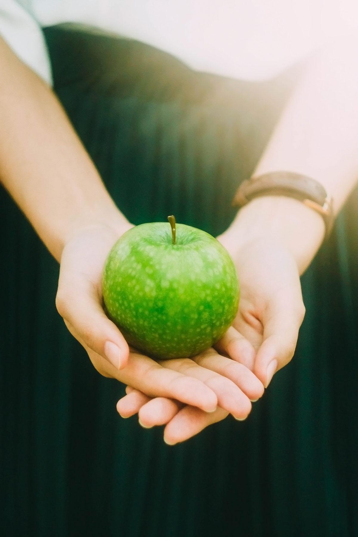chica sujetando una manzana